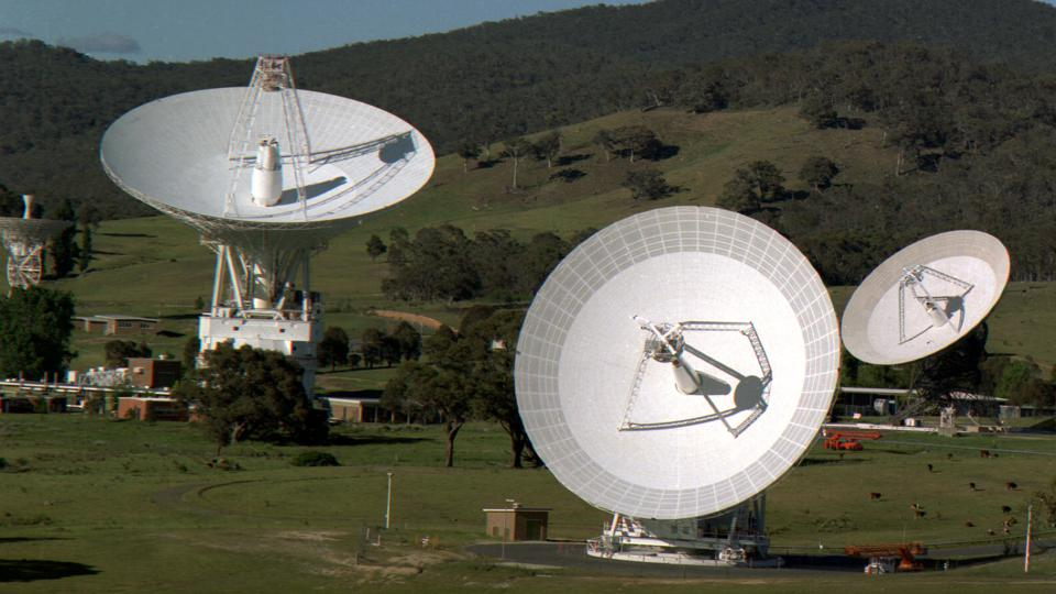 Color photo of 4 radio dish antennas with a green hill in the background