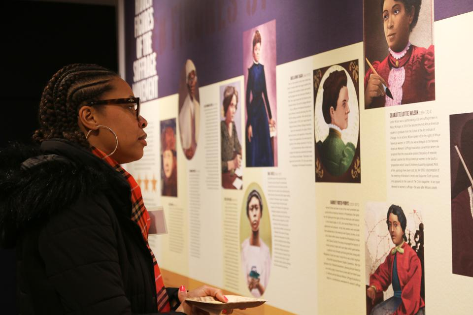 A visitor examines 'Hidden Figures of the Suffragist Movement' mural at Brandywine River Museum of Art.