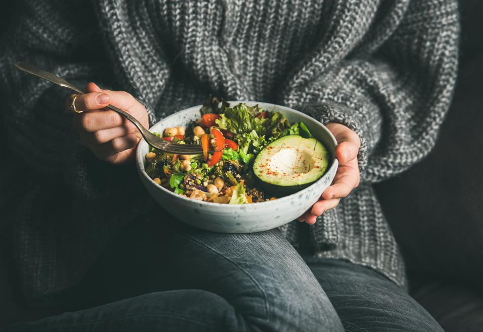 Woman in sweater eating fresh salad, avocado, beans and vegetables