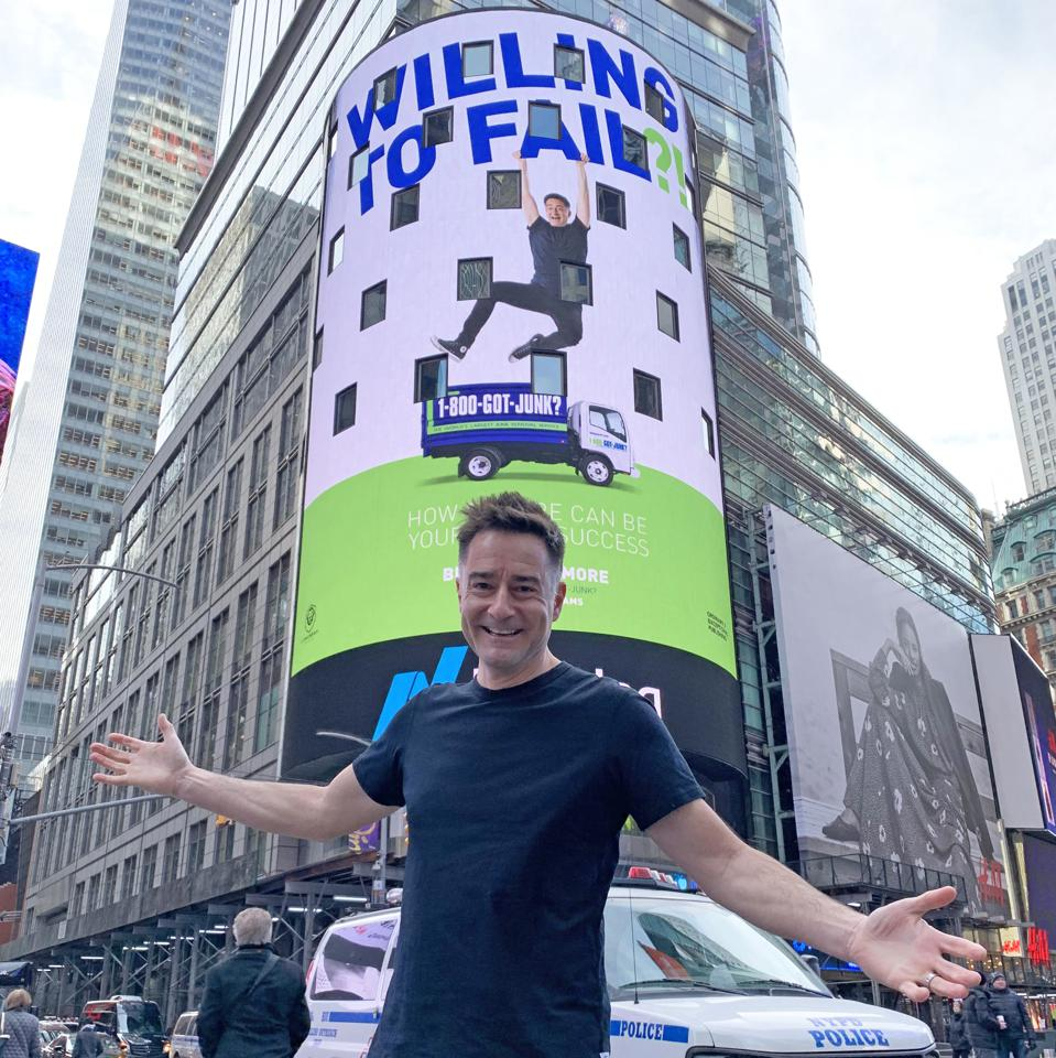 Brian Scudamore in front of aNYC billboard showing his book: WTF?! Willing to Fail.