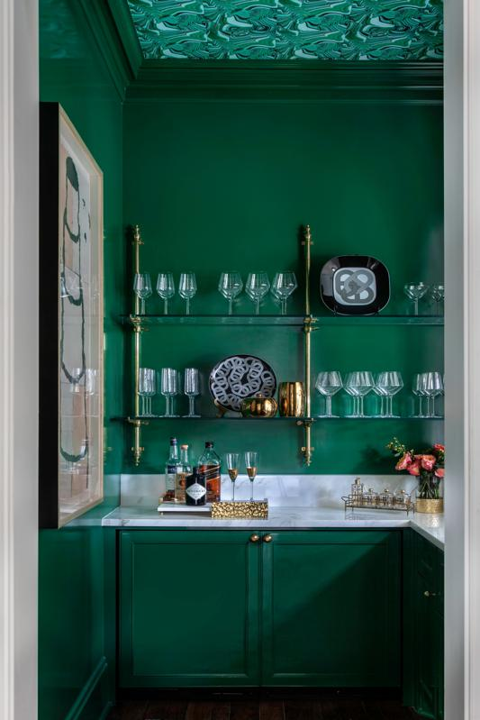 Home bar with green walls, green cabinetry, and wallpapered ceiling.