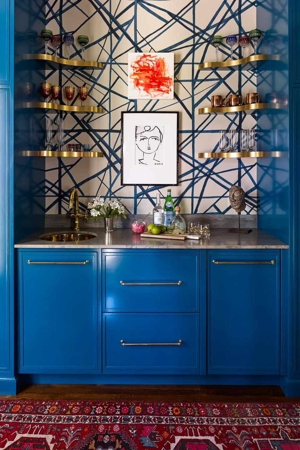 Home bar with blue cabinetry and metal hardware and gold shelving.