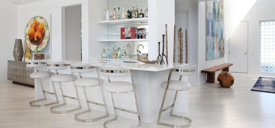 White bar with white bar stools and metal accents.