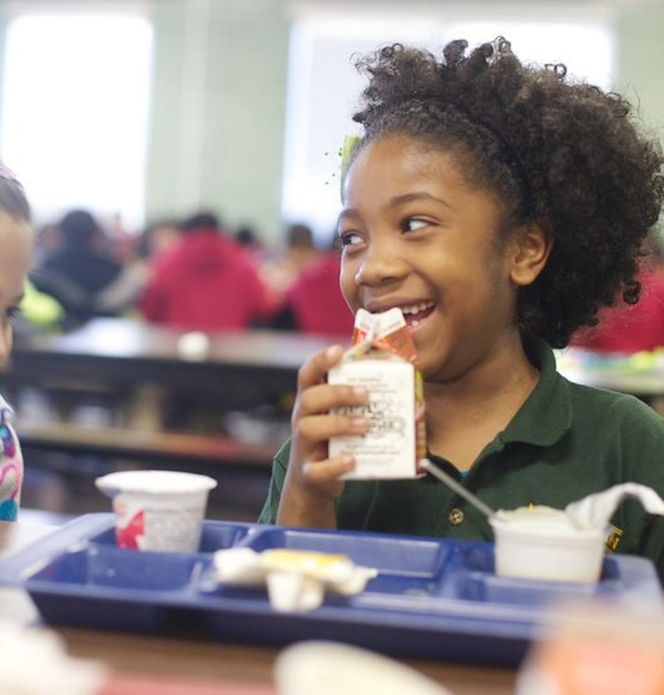 Happy KIPP public charter school student eating lunch