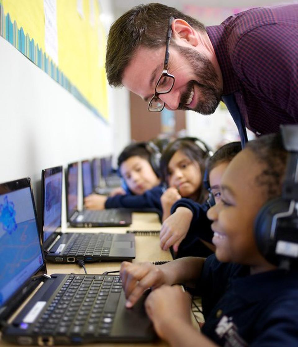 KIPP public school teacher works with students on computers