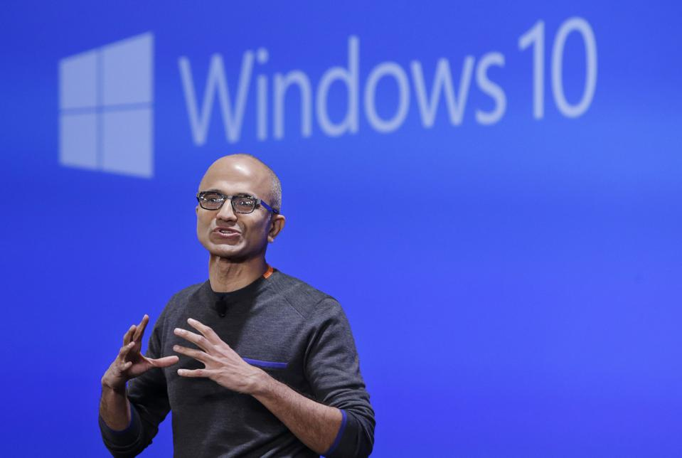 Satya Nadella, Microsoft CEO, in front of a Windows 10 banner