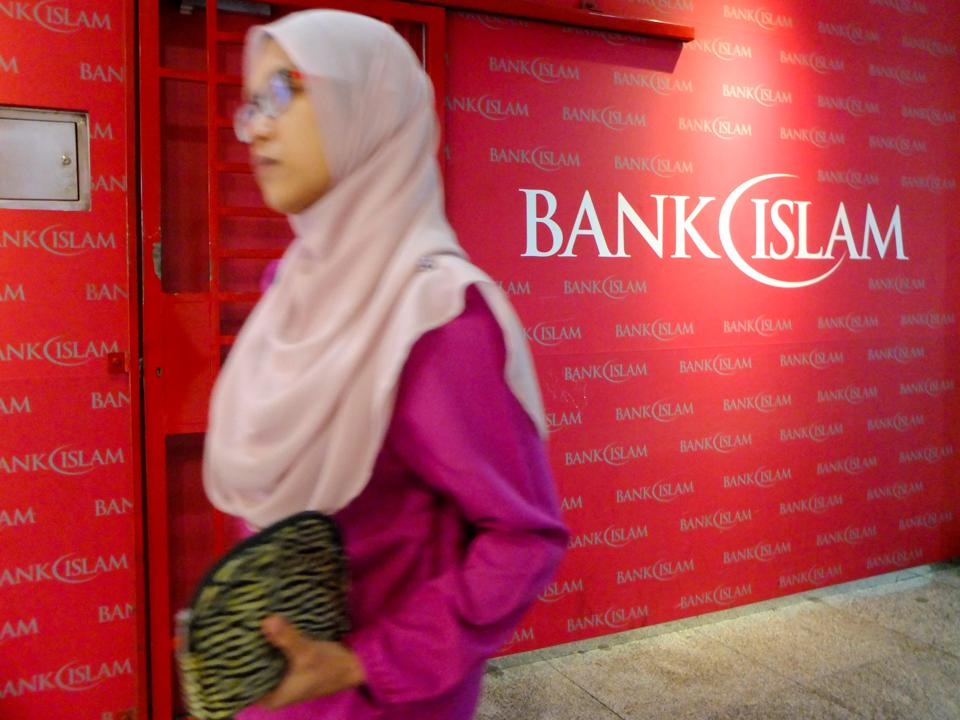 A muslim women is seen passing a Bank Islam sign.