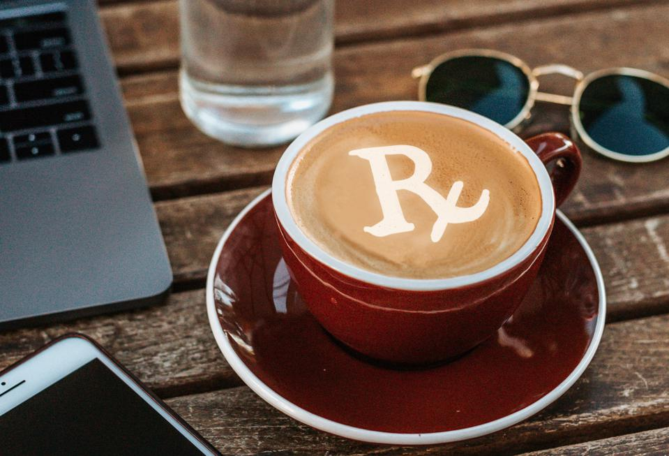 A cafe with a latte with a Rx sign drawn in the latte foam.