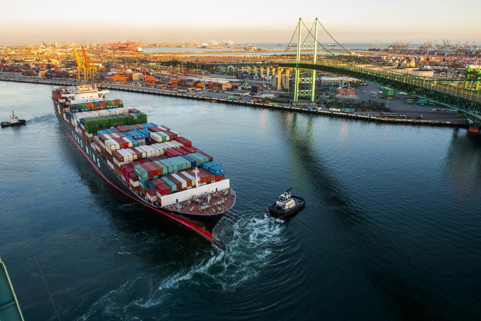 A tugboat assists a container ship in the Port of Los Angeles's main turning basin.