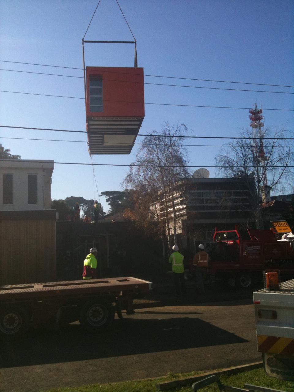The module is carefully lifted high above the electrical wires.