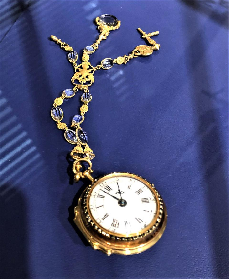 A pocket watch for women attached to a bejeweled chain