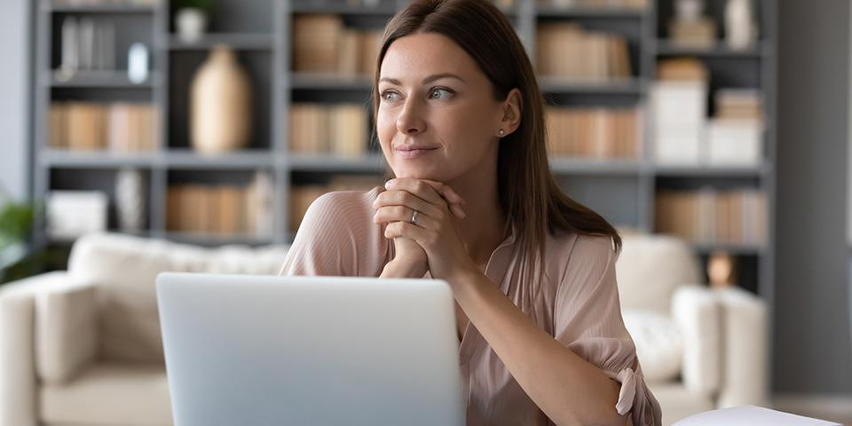 Young dreamy woman sitting at table, distracted from computer work.