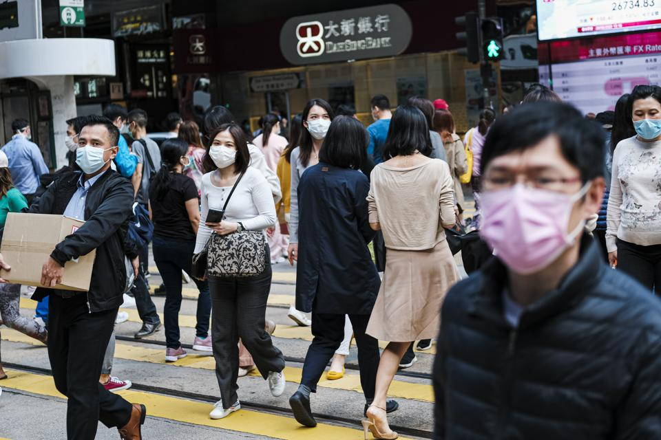 People with surgical face masks cross the street in Central...