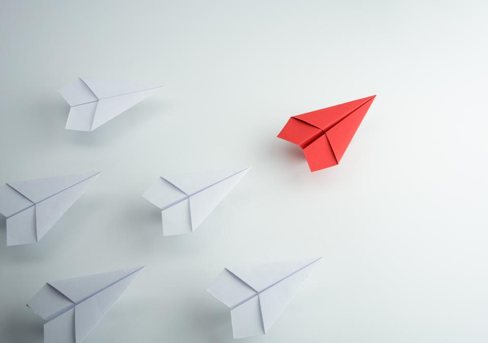 A red paper airplane leads a flock of white paper airplanes.
