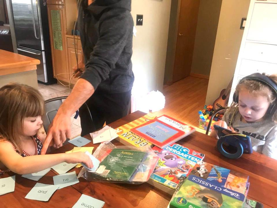 Two young girls sitting at a wooden table with books, word cards, and electronics.