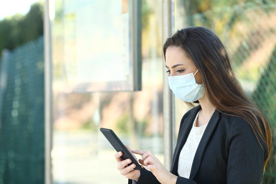 Woman wearing a protective mask using phone.
