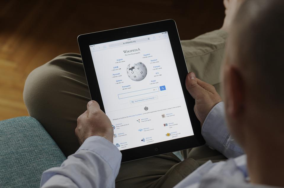 A man is seen looking at a Wikipedia page on an iPad on October 24, 2017. Apple iPad Details and Popular iOS app.