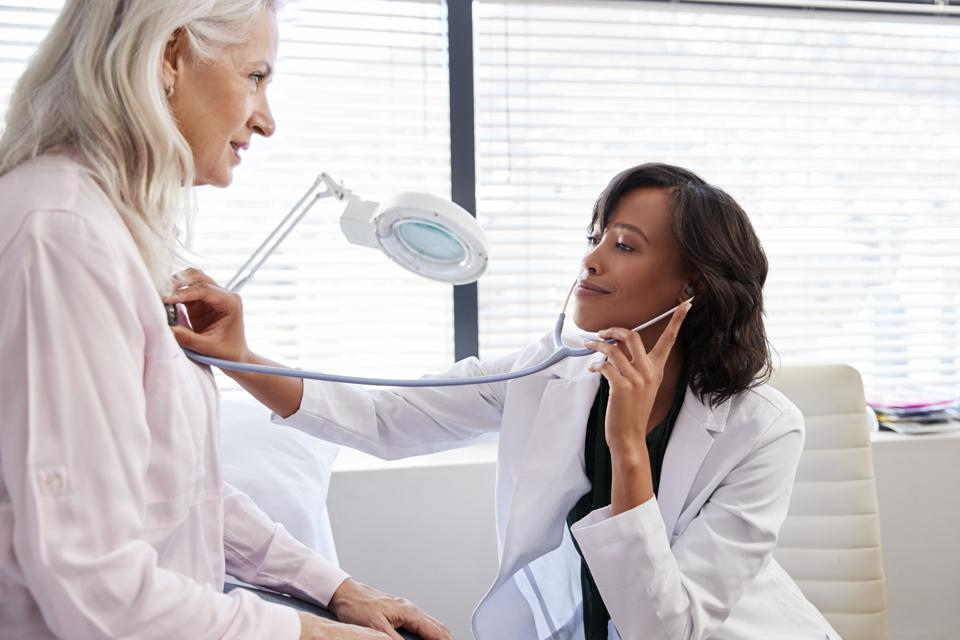 Woman Patient Having Medical Exam With Female Doctor In Office