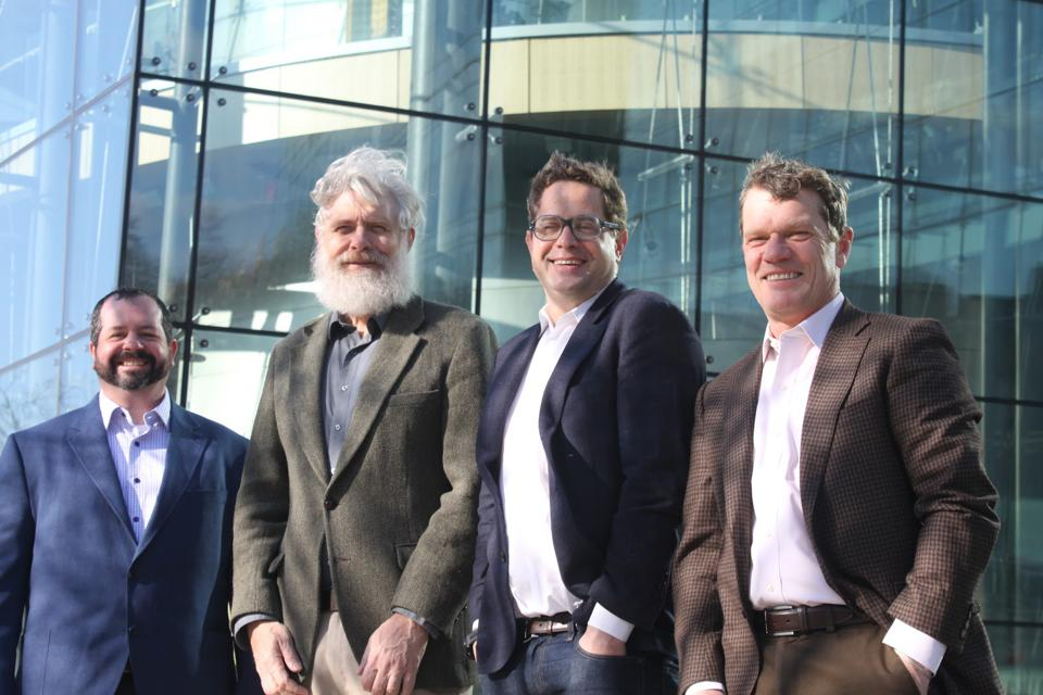 Four scientists in front of a glass building. Looks like a windy day.