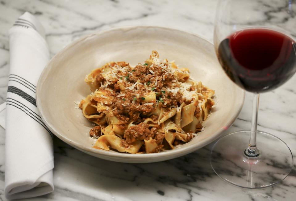 Ragu on a plate with egg noodles, next to a glass of red wine.