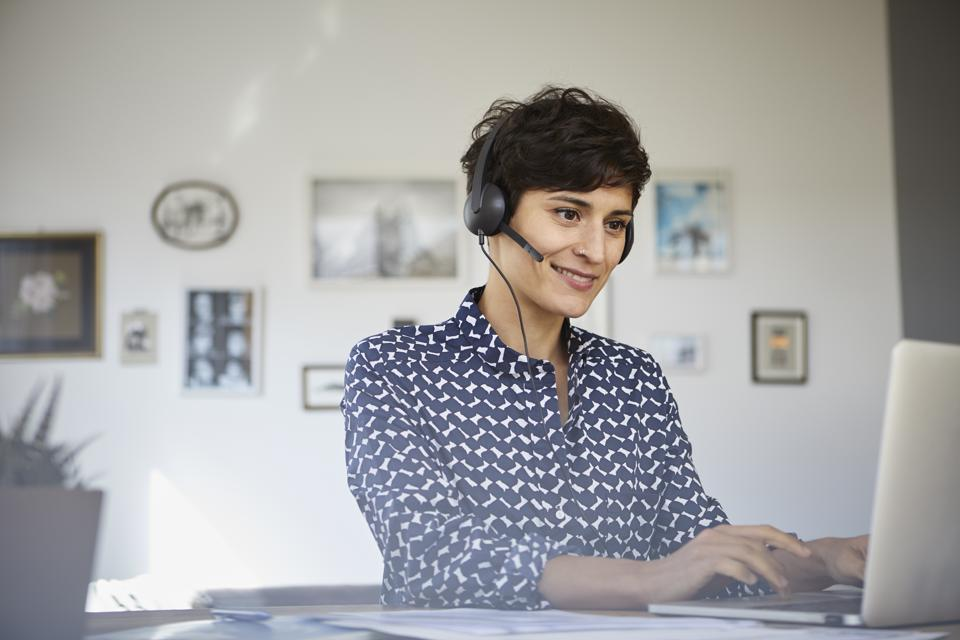 Smiling woman at home with headset using laptop