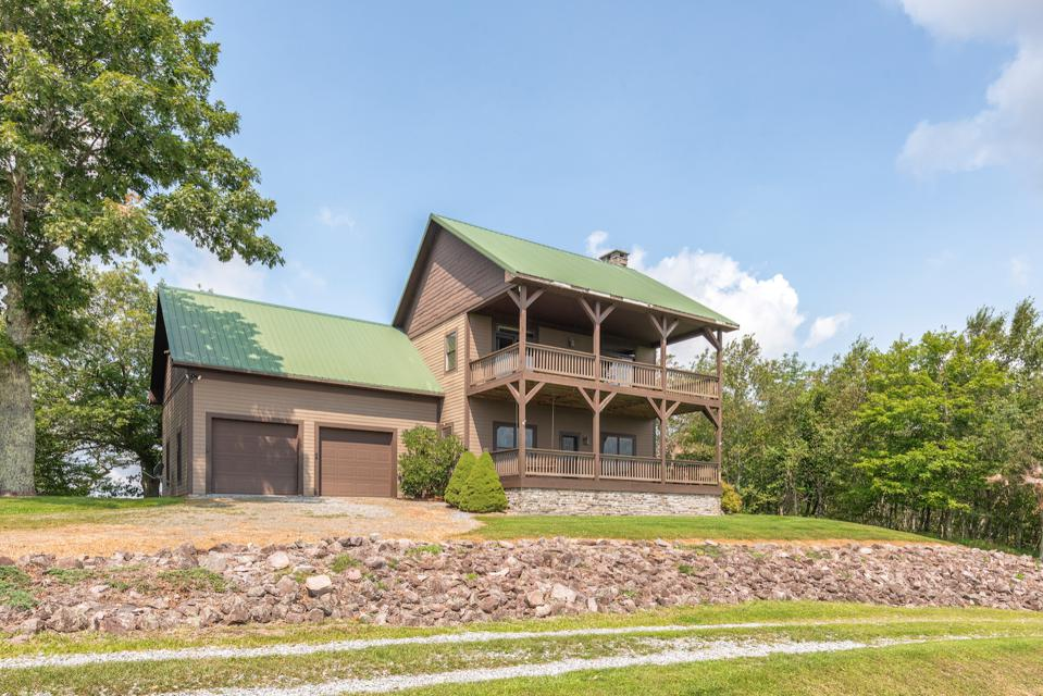 Cabin 2 has four bedrooms, a stone fireplace and full-length porches on two levels.