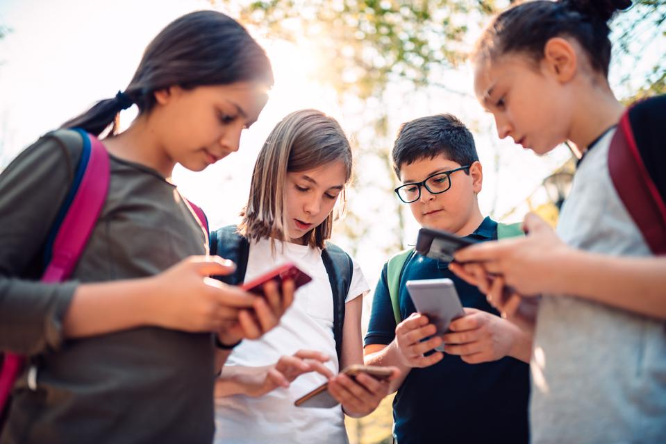 Kids playing video games on smart phone after school
