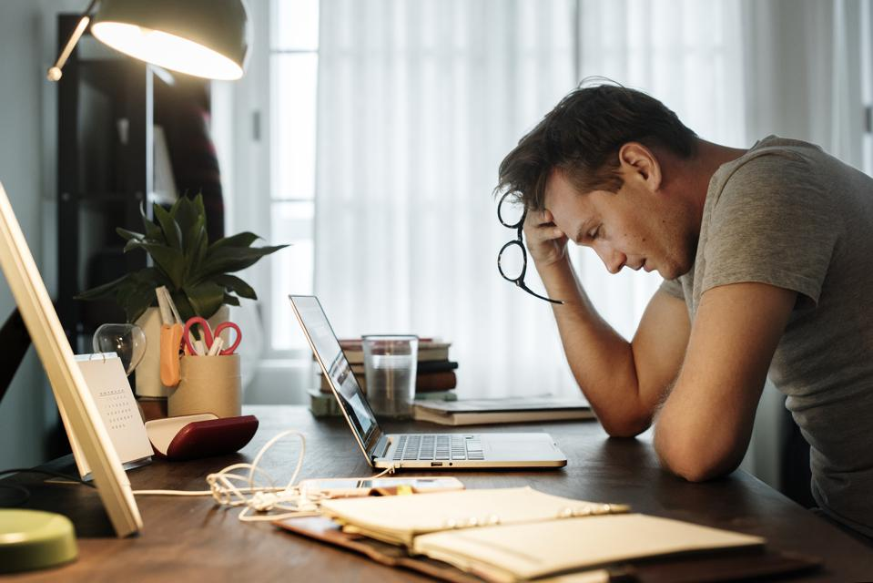 Man stressed while working on laptop