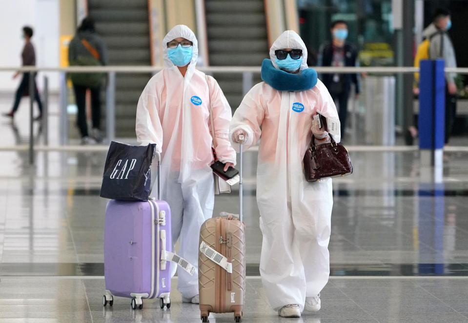 Passengers wearing protective suits.