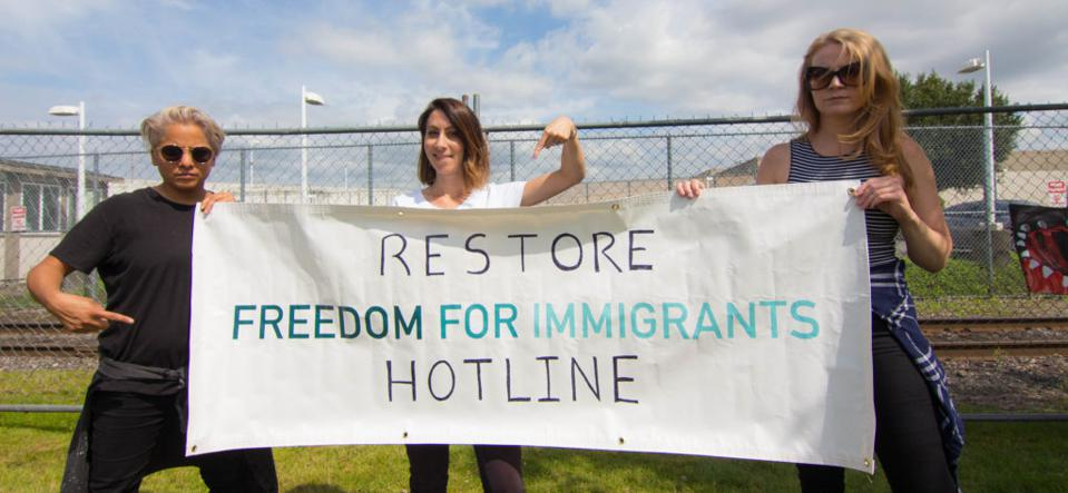 Changemakers with a sign to restore help for immigrants in detention