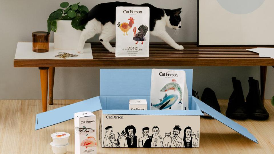 A box of products from the new e-commerce brand Cat Person, with a black and white cat walking next to the box.