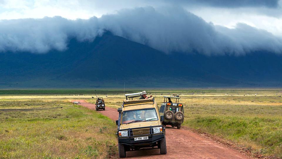 Arusha Region, Ngorongoro Conservation Area, A Safari Vehicle Crosses The Savannah Plain O