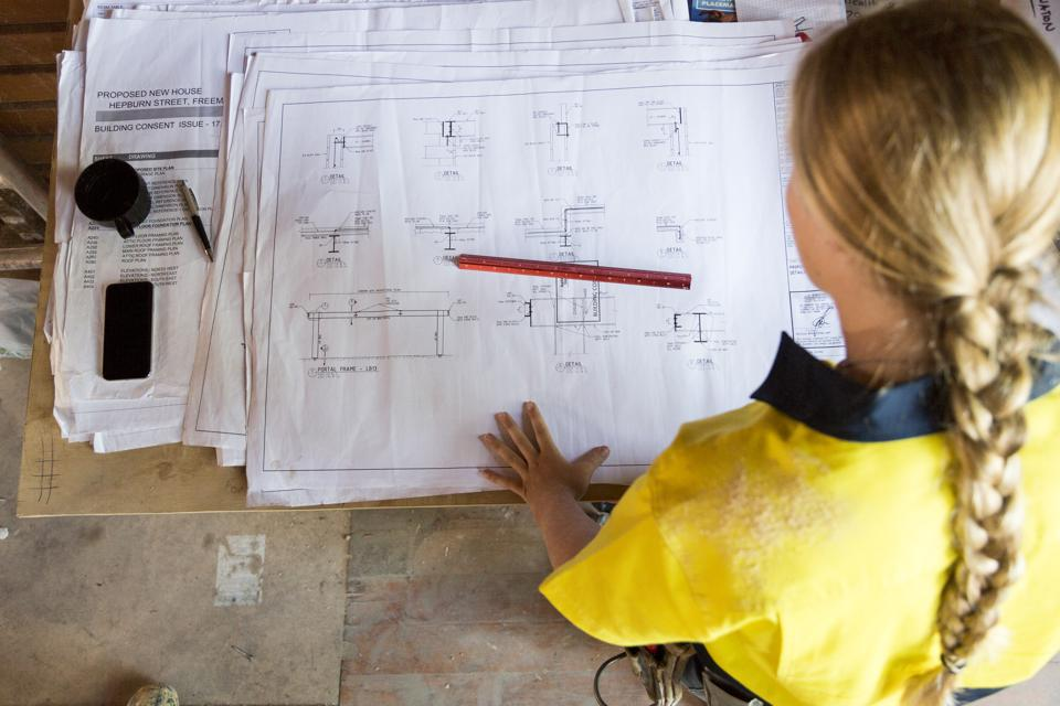 A female construction worker looks at site plans