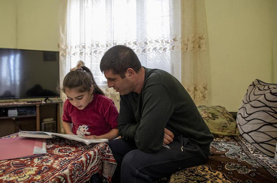 Homework has taken on new meaning since coronavirus has shut down schools around the world. Here, Hripsime, 9, (left) gets an assist with her studies from her father, Vladimir, at the family's home in Gyumri, Armenia.
