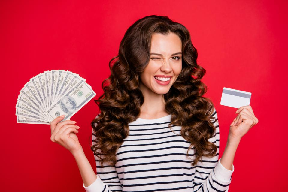 Portrait of nice attractive cheerful positive funky wavy-haired lady wearing striped pullover holding in hands plastic card and fan of hundreds usd isolated over bright vivid shine red background