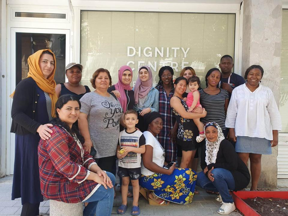 A group of refugees and volunteers stand outside the Dignity Center