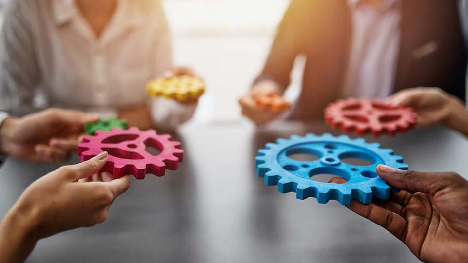 Hands holding different colored gears at a table.