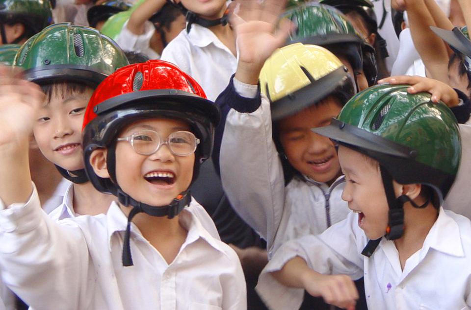 Children wearing helmets made by the Asia Injury Prevention Foundation.