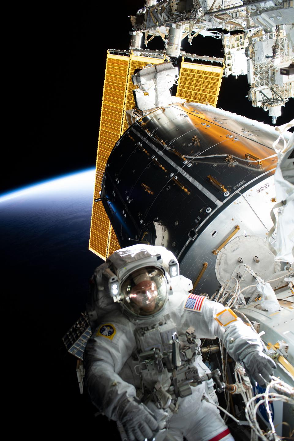 Astronaut Nick Hague tethered to the International Space Station.