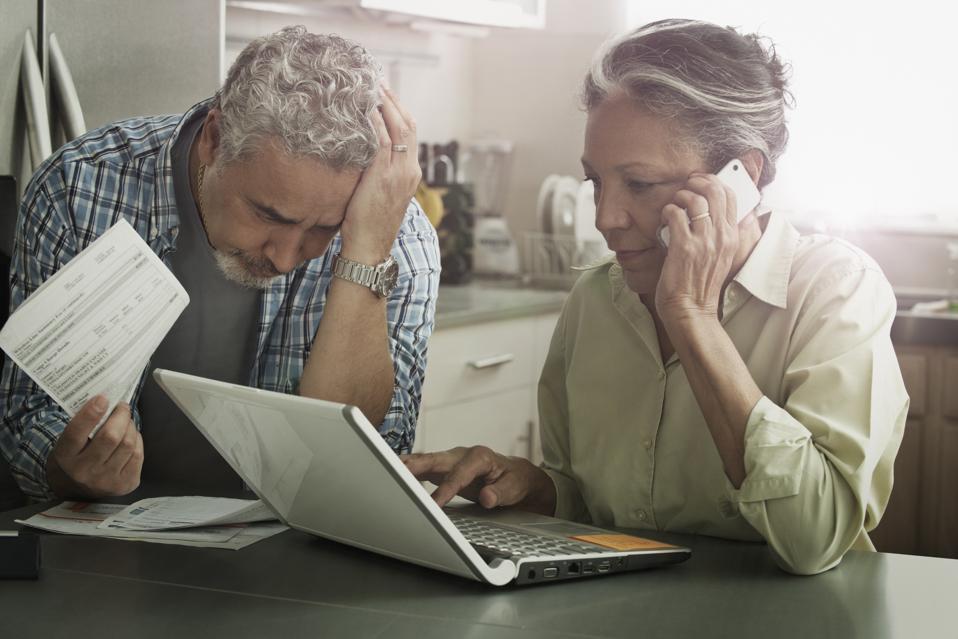 Stressed Hispanic couple paying bills on laptop