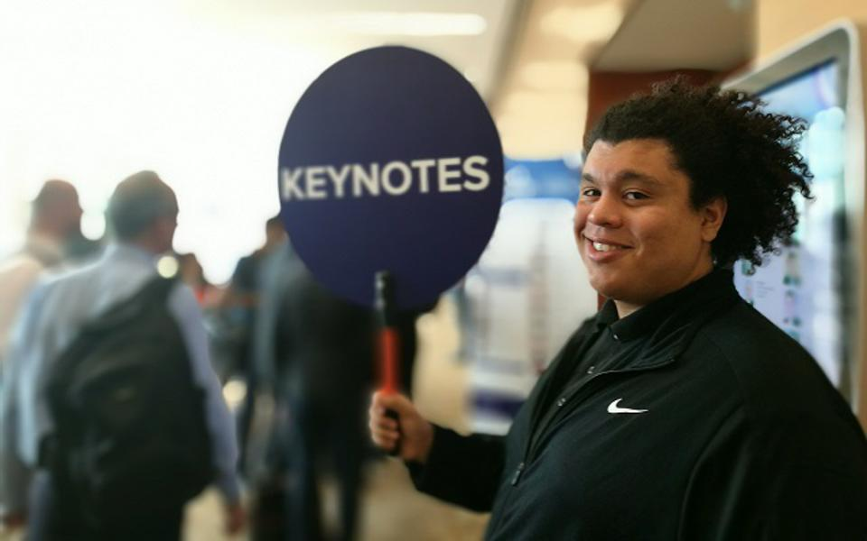 A young man holding up a 'lollipop' sign that reads KEYNOTES to invite people into a conference room.