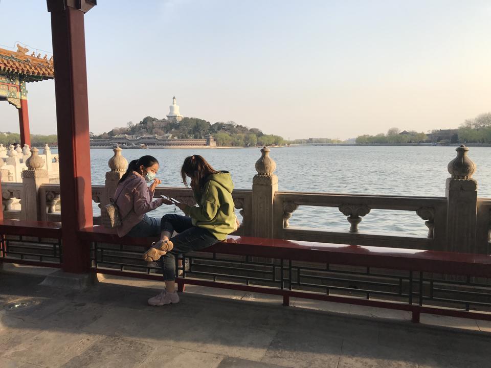 Mother and daughter visit Beihai Park in Beijing during the coronavirus crisis.