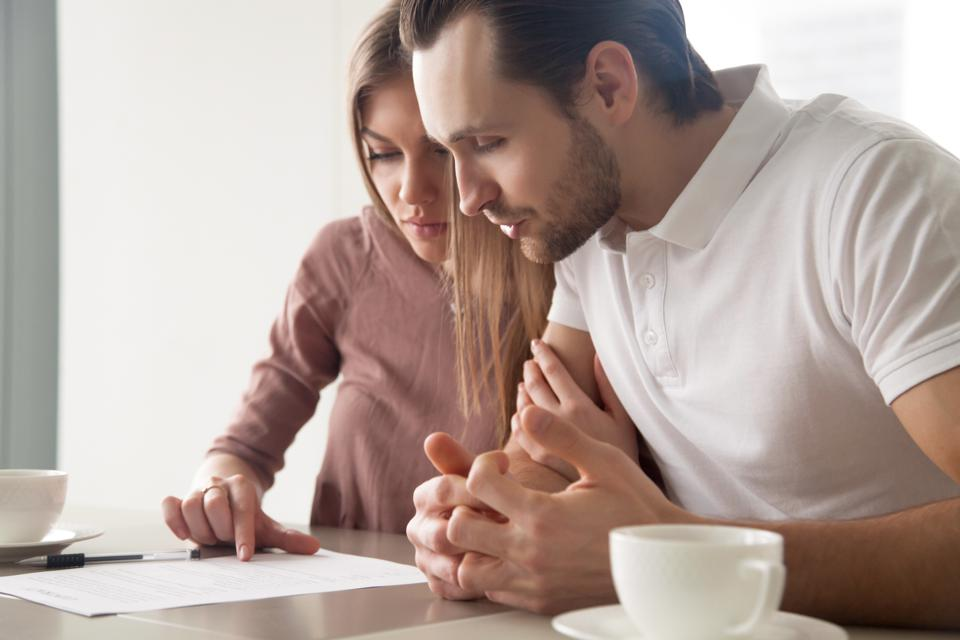 Serious married couple with papers, considering loan offer, calculating bills