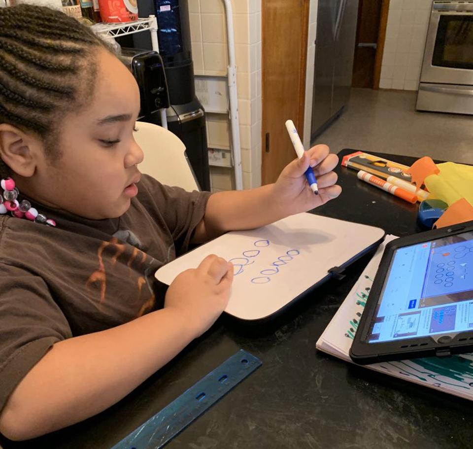 A young girl with braids works on math with a whiteboard and an iPad by a washing machine.