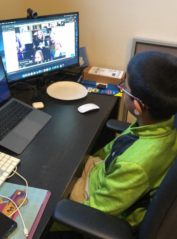 A boy in a green windbreaker video chats with his teacher and peers at a desk.