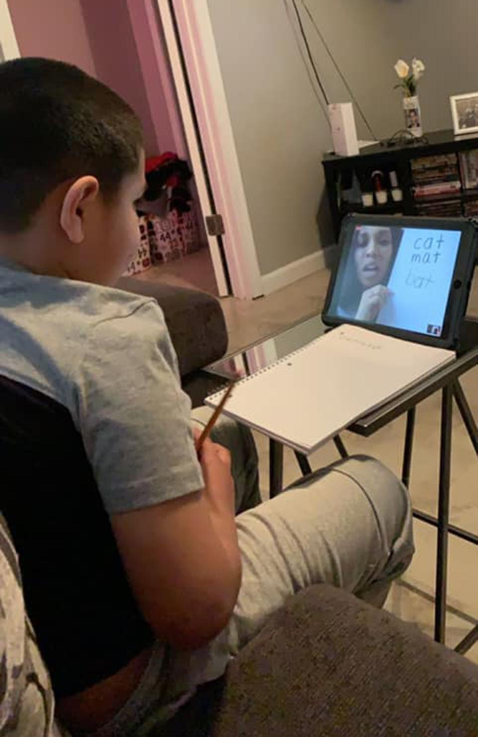 A boy takes notes and video chats with his ELA teacher.