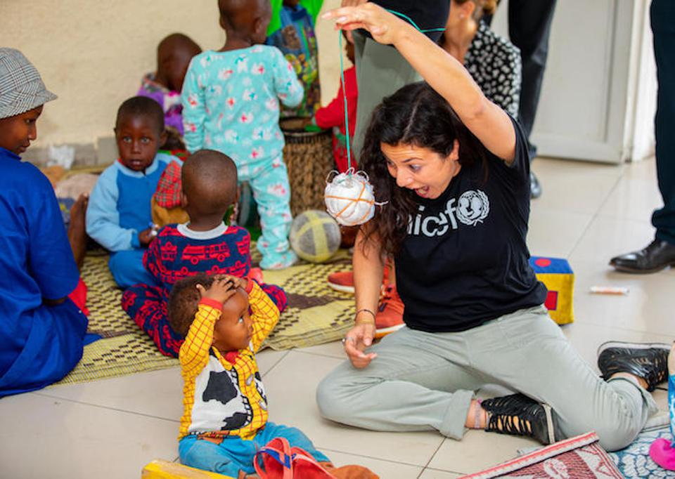 Casey Rotter, founder and managing director of UNICEF NextGen, plays with a child at the UNICEF-supported cross-border Early Childhood Development center in Rubavu, Rwanda.