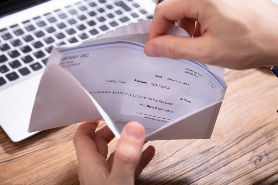 Person's Hand Removing Paycheck From The Envelope