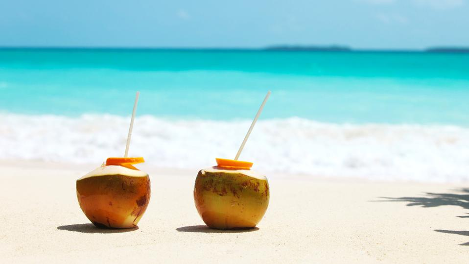 two coconut drinks on tropical beach vacation