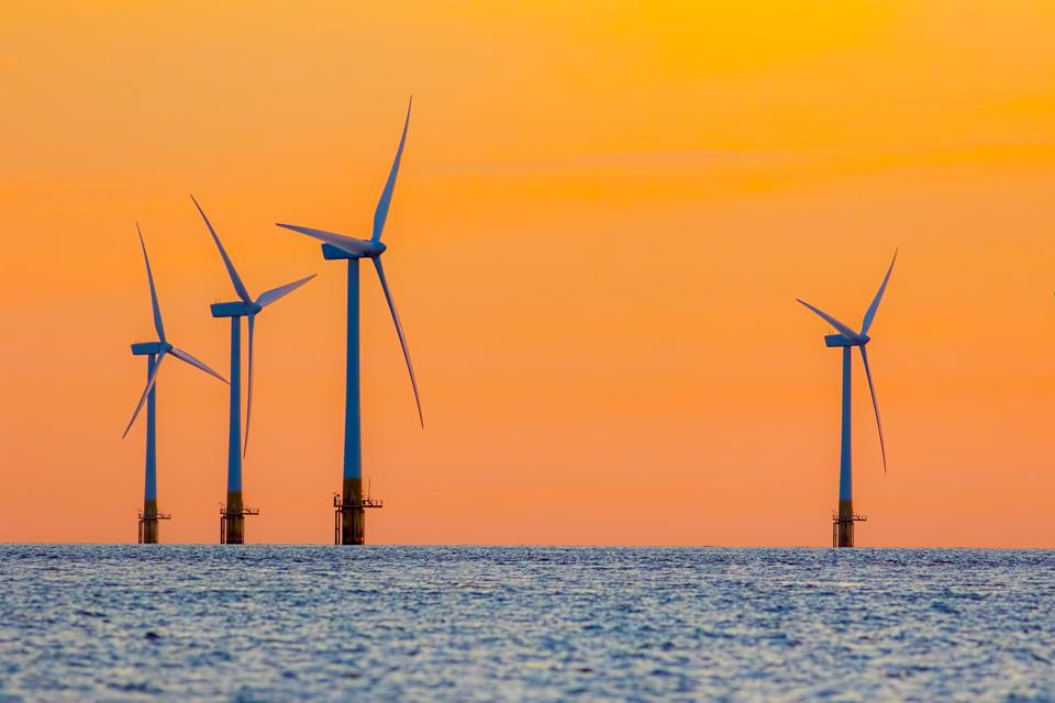 Offshore wind farm energy turbines at dawn.
